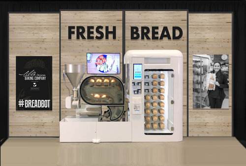 Der BreadBot steht vor einer Wand, auf der Fresh Bread zu lesen ist.